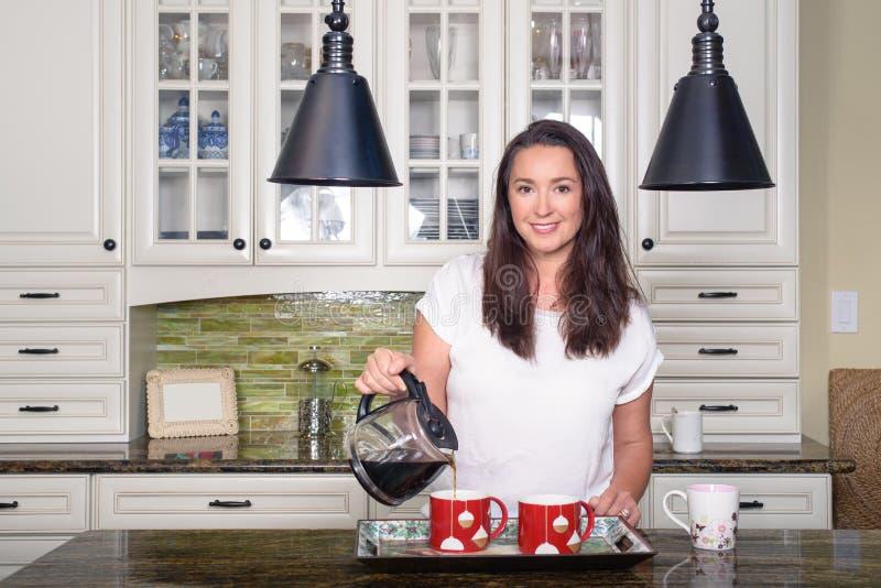Mulher atrativa que derrama o café caseiro para dois na cozinha ensolarada moderna imagens de stock royalty free