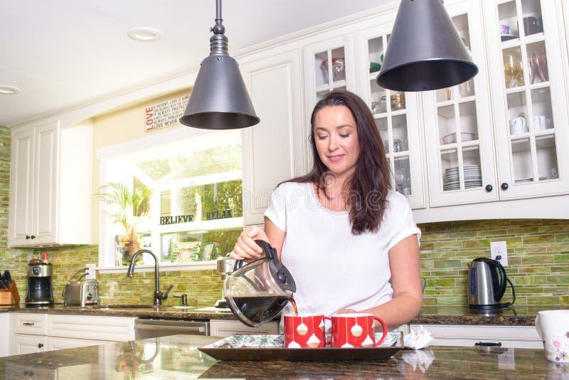 Mulher atrativa que derrama o café caseiro para dois na cozinha ensolarada moderna fotografia de stock royalty free