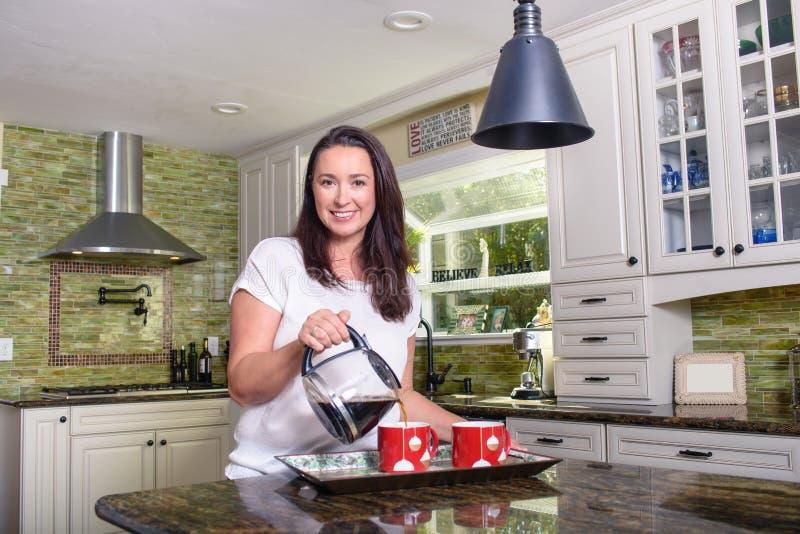 Mulher atrativa que derrama o café caseiro para dois na cozinha ensolarada moderna foto de stock royalty free