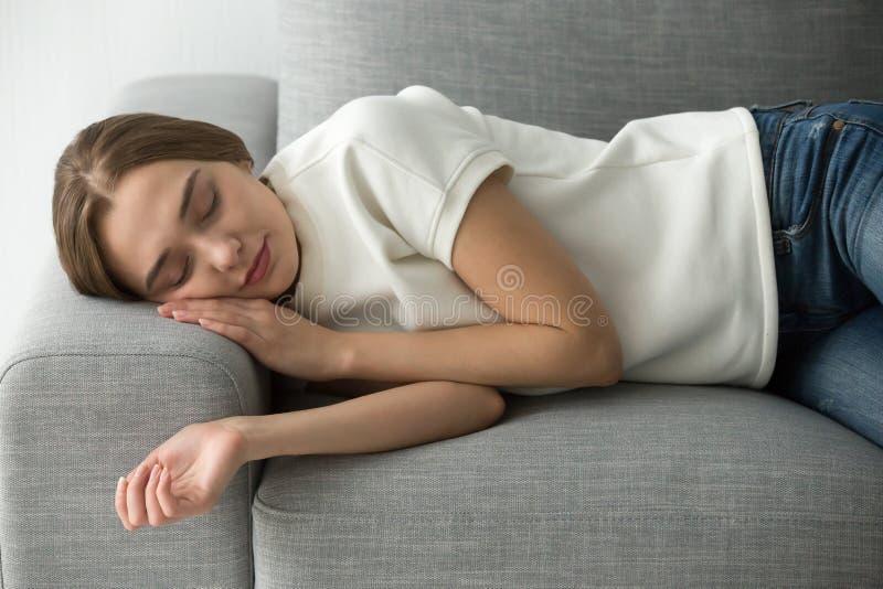 Mulher atrativa que dorme no sofá macio confortável imagem de stock