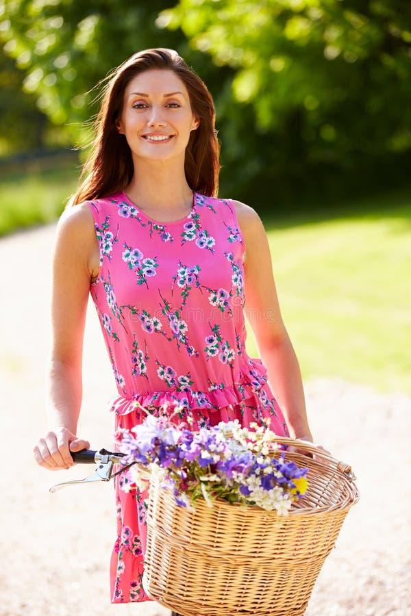 Mulher atrativa que empurra a bicicleta fotografia de stock