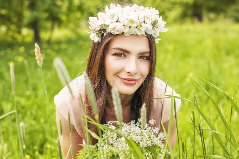 Mulher atrativa que encontra-se no prado da grama verde e das flores fotografia de stock royalty free