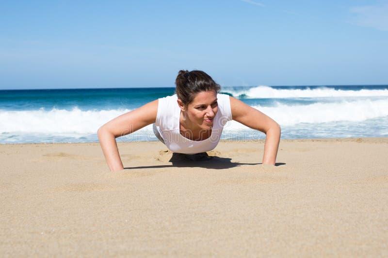 Mulher atrativa que faz impulso-UPS na praia foto de stock royalty free