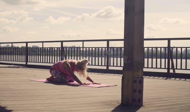 A mulher atrativa que faz a ioga exercita fora fotografia de stock royalty free
