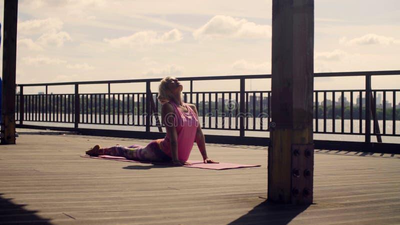 A mulher atrativa que faz a ioga exercita fora foto de stock royalty free