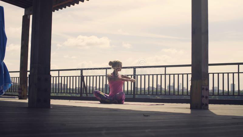 A mulher atrativa que faz a ioga exercita fora foto de stock