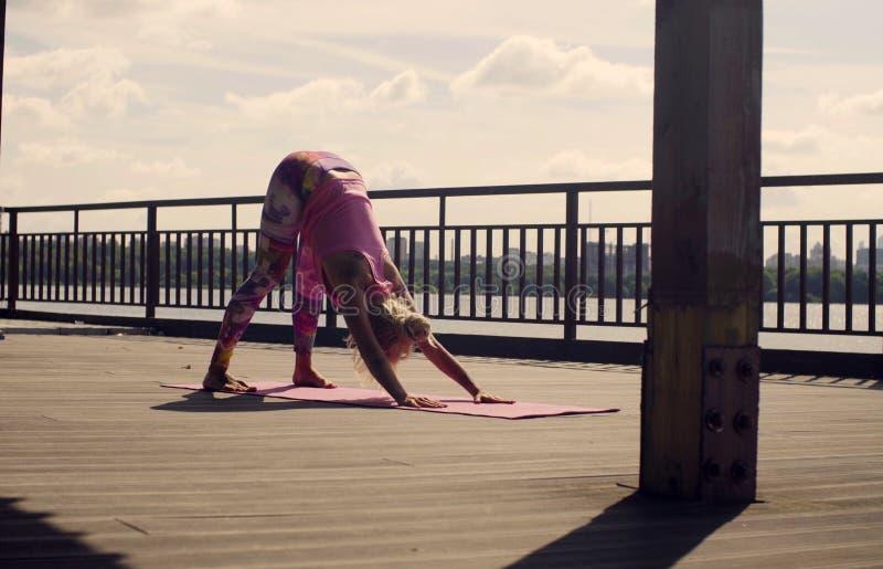 A mulher atrativa que faz a ioga exercita fora fotografia de stock