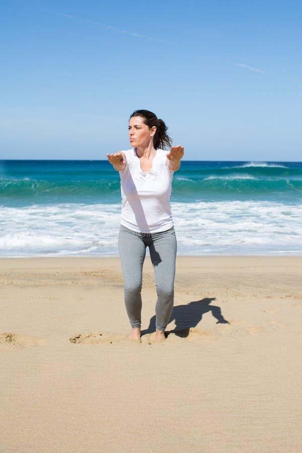 Mulher atrativa que faz o cruz-ajuste na praia fotos de stock royalty free