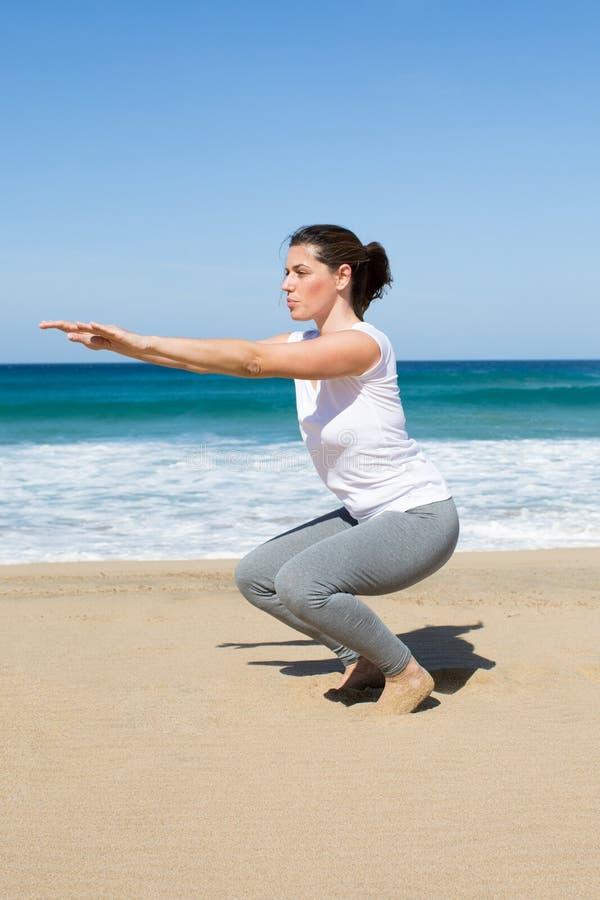 Mulher atrativa que faz o cruz-ajuste na praia fotos de stock