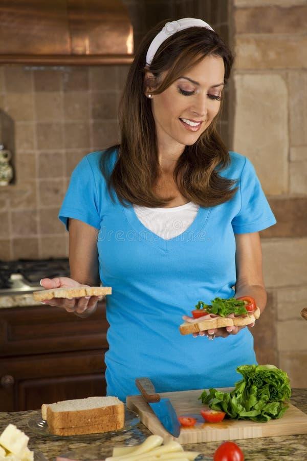 Mulher atrativa que faz sanduíches na cozinha Home fotos de stock