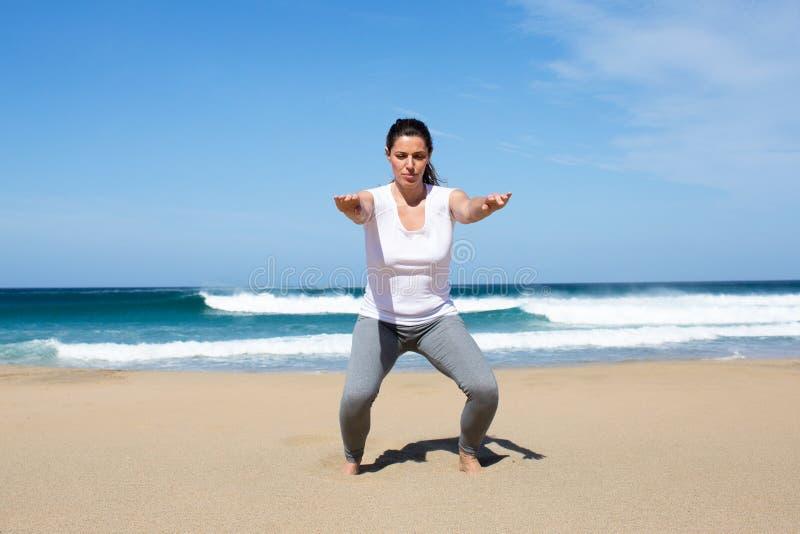 Mulher atrativa que faz sentar-UPS na praia imagem de stock royalty free