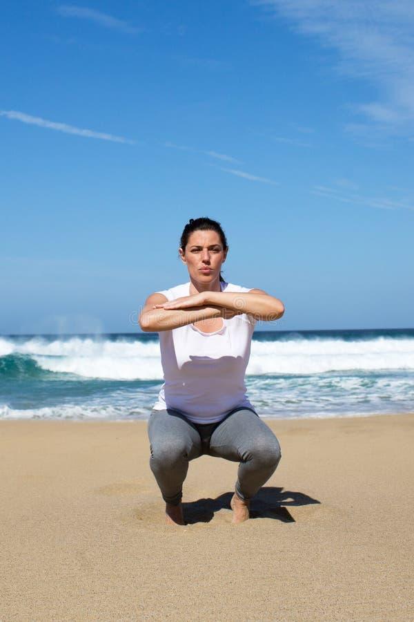 Mulher atrativa que faz sentar-UPS na praia fotografia de stock royalty free