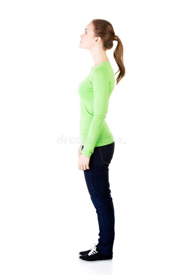 Mulher atrativa que levanta-se e que olha. Vista lateral. imagens de stock