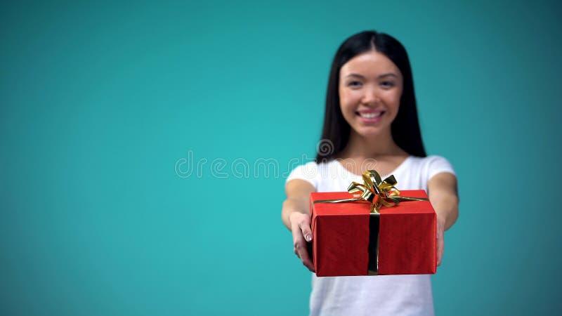 Mulher atrativa que mostra o giftbox na câmera, surpresas agradáveis, cumprimentos de b-dia imagens de stock
