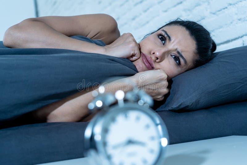 A mulher atrativa que olha fixamente no despertador que tenta dormir sentimento forçou deprimido e sem sono imagens de stock royalty free