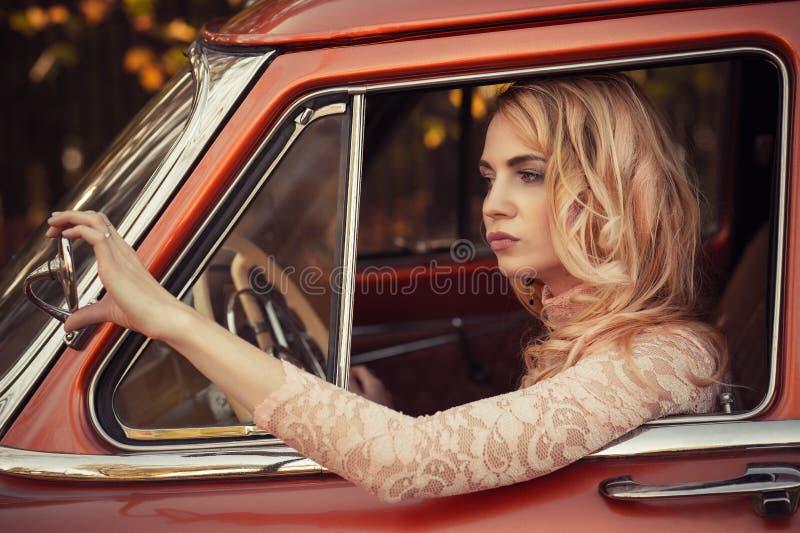 Mulher atrativa que olha o carro retro do espelho lateral imagens de stock royalty free