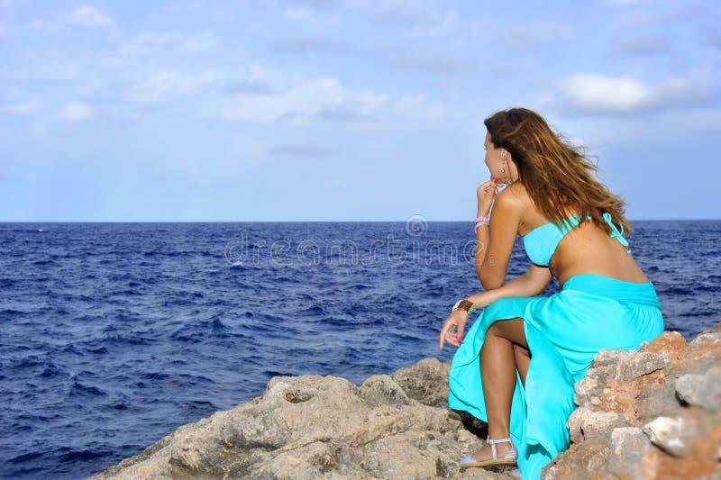 A mulher atrativa que olha o horizonte de mar pensativo do penhasco da rocha relaxa dentro o conceito fotografia de stock royalty free