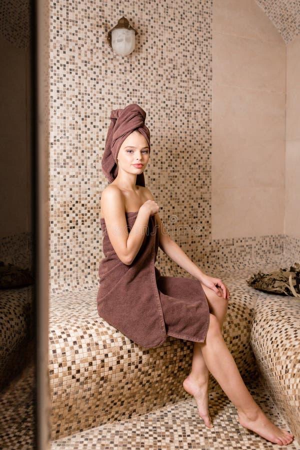 Mulher atrativa que relaxa em um hammam - banho de vapor turco com o azulejo no estilo romano imagens de stock