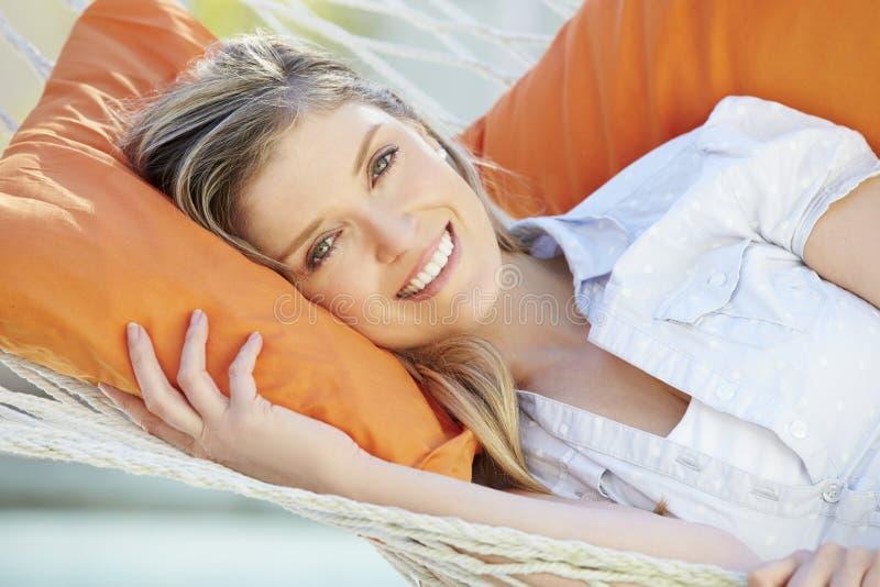 Mulher atrativa que relaxa na rede do jardim imagem de stock