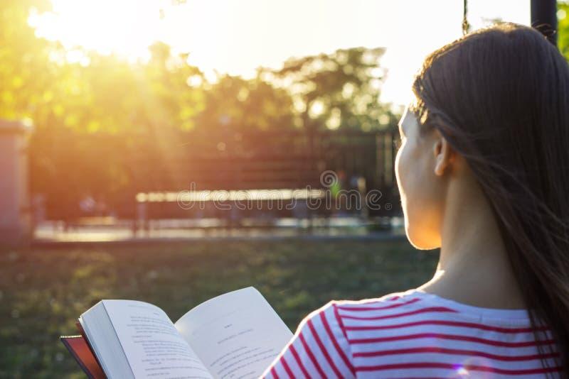 Mulher atrativa que senta-se fora em um banco que lê um livro no por do sol Vista traseira fotografia de stock royalty free