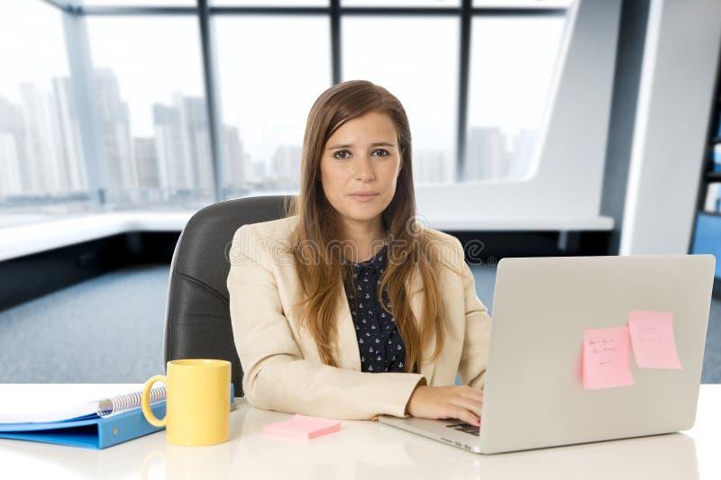 Mulher atrativa que senta-se na cadeira do escritório que trabalha na mesa do laptop imagens de stock
