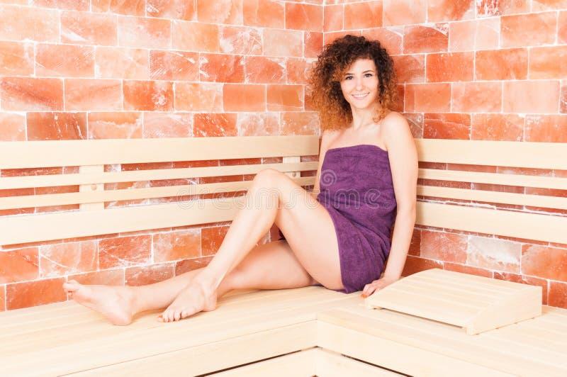 Mulher atrativa que sorri ao sentar-se na sauna imagem de stock royalty free