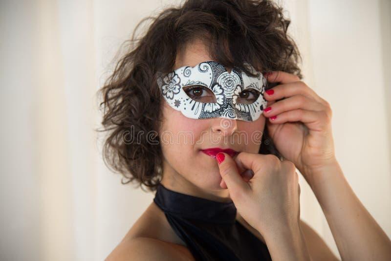 Mulher atrativa que sorri com máscara do carnaval fotografia de stock