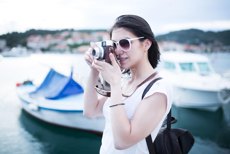 Mulher atrativa que toma imagens com a câmera retro do vintage que ri e que sorri feliz durante o curso das férias das férias de  imagem de stock royalty free