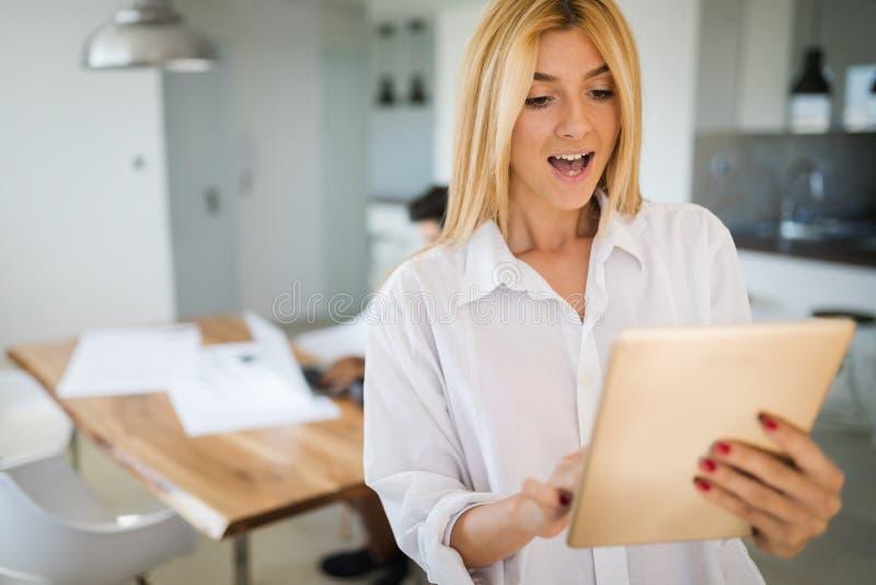 Mulher atrativa que trabalha em uma tabuleta em um escritório domiciliário imagem de stock royalty free