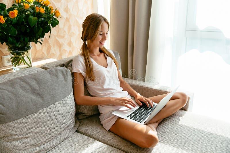 Mulher atrativa que trabalha no portátil ao sentar-se no sofá em casa imagens de stock