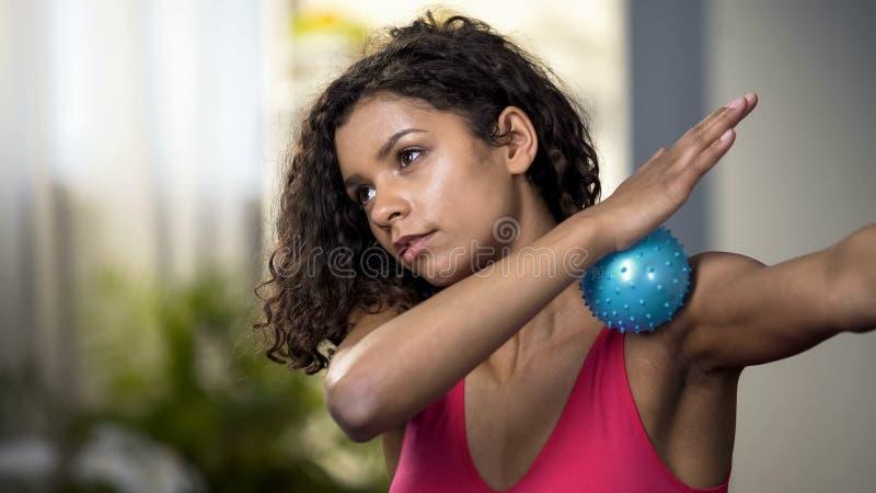 Mulher atrativa que usa-se fazendo massagens a bola, abrandamento dos músculos, circulação sanguínea fotografia de stock royalty free