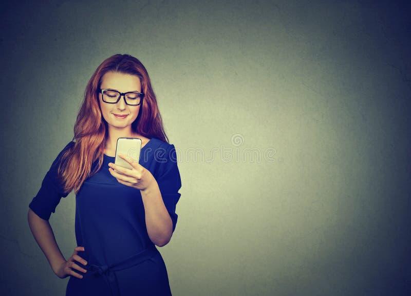 Mulher atrativa que usa texting esperto do telefone fotografia de stock royalty free