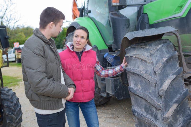 Mulher atrativa que vende o trator brandnew ao fazendeiro do novato fotos de stock