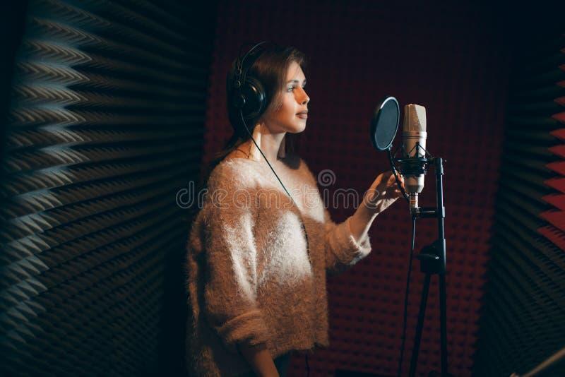 Mulher atrativa séria nova que canta em um estúdio de gravação foto de stock