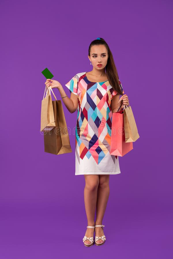 Mulher atrativa 20s no vestido que mantém os pacotes da compra e o cartão de crédito verde da exibição isolados sobre o fundo rox foto de stock royalty free