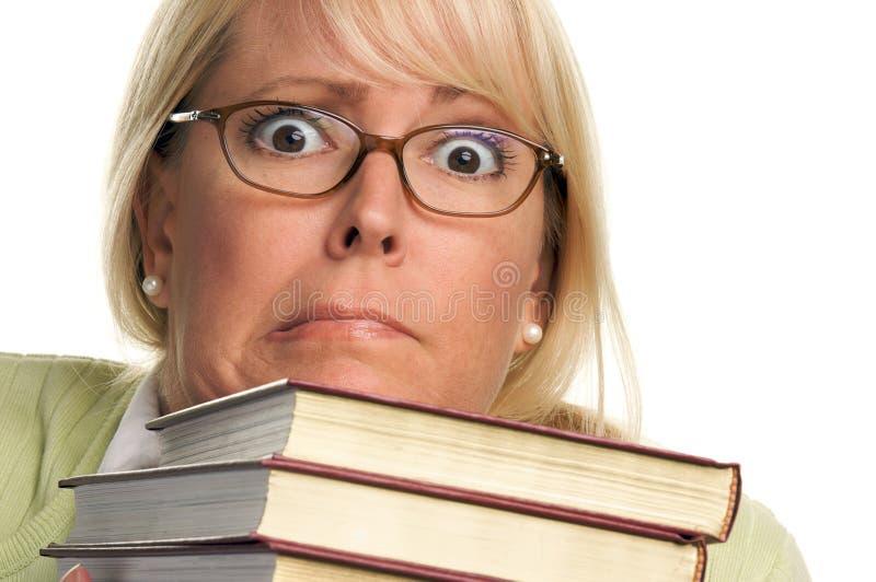 Mulher atrativa Scared com a pilha de livros imagem de stock