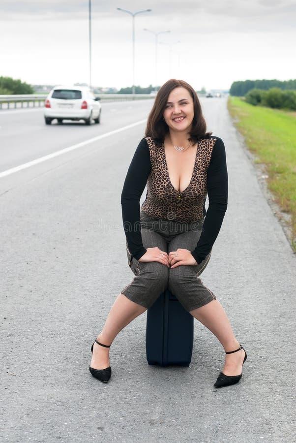 A mulher atrativa senta-se na escadaria perto da estrada imagens de stock