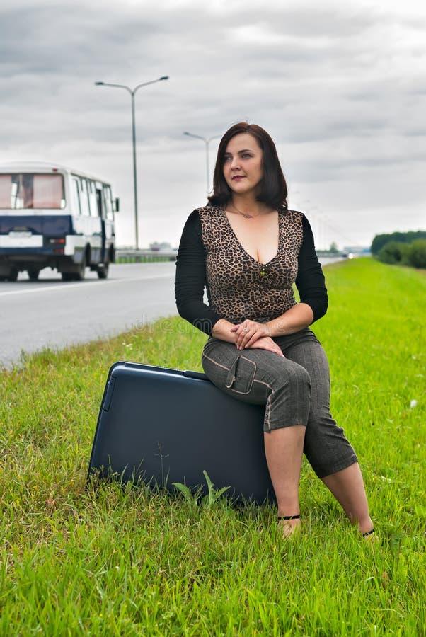 A mulher atrativa senta-se na escadaria perto da estrada fotografia de stock