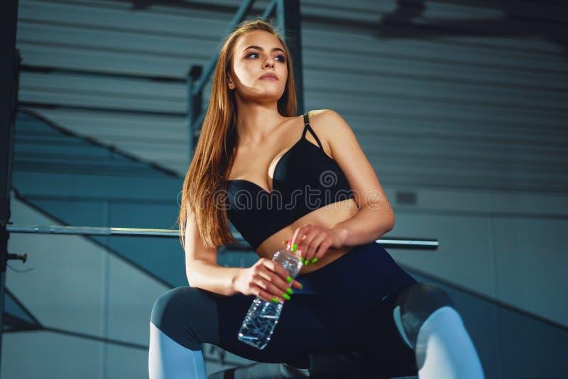 Mulher attracrive nova do esporte que senta-se com garrafa de ?gua foto de stock