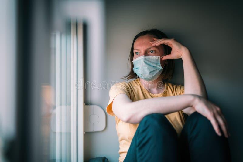 Mulher autoisolada durante surto de vírus olhando pela janela foto de stock royalty free