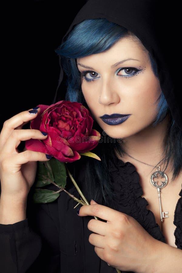 A mulher azul do cabelo da composição com o tampão preto da capa e aumentou fotografia de stock royalty free