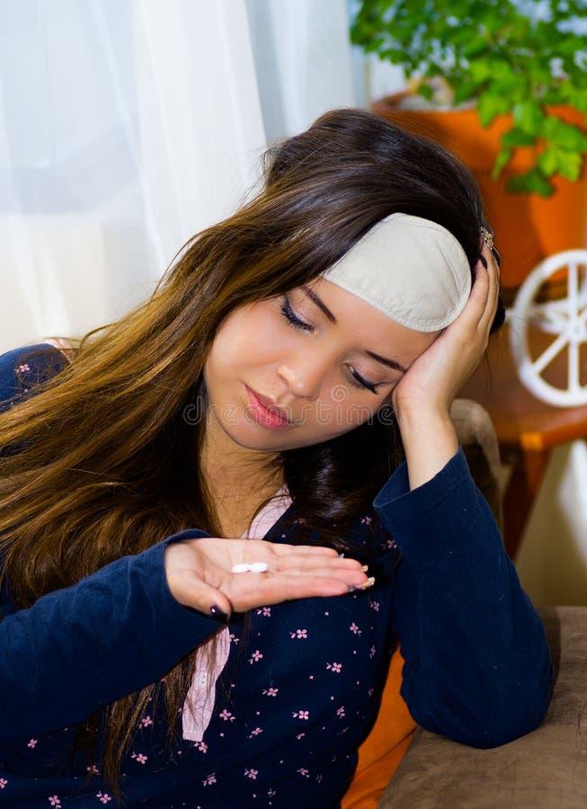 Mulher bêbada com um valor máximo de concentração no trabalho do olho do sono em sua cabeça, com um comprimido em sua mão, manute imagens de stock