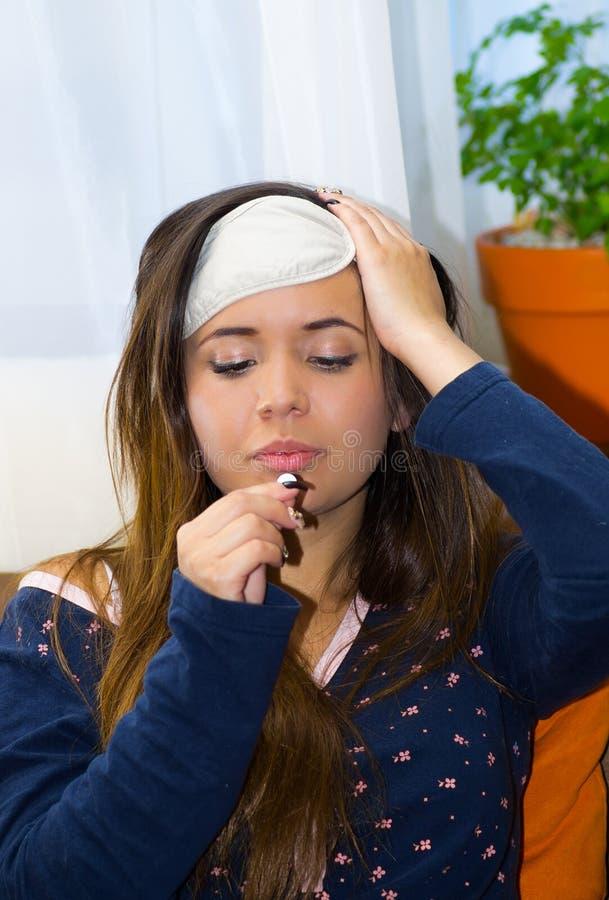 Mulher bêbada com um valor máximo de concentração no trabalho do olho do sono em sua cabeça, com um comprimido em sua mão, manute fotografia de stock