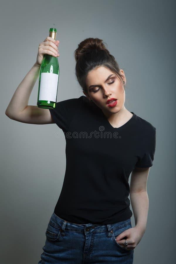 Mulher bêbada que guarda a garrafa de vinho fotografia de stock