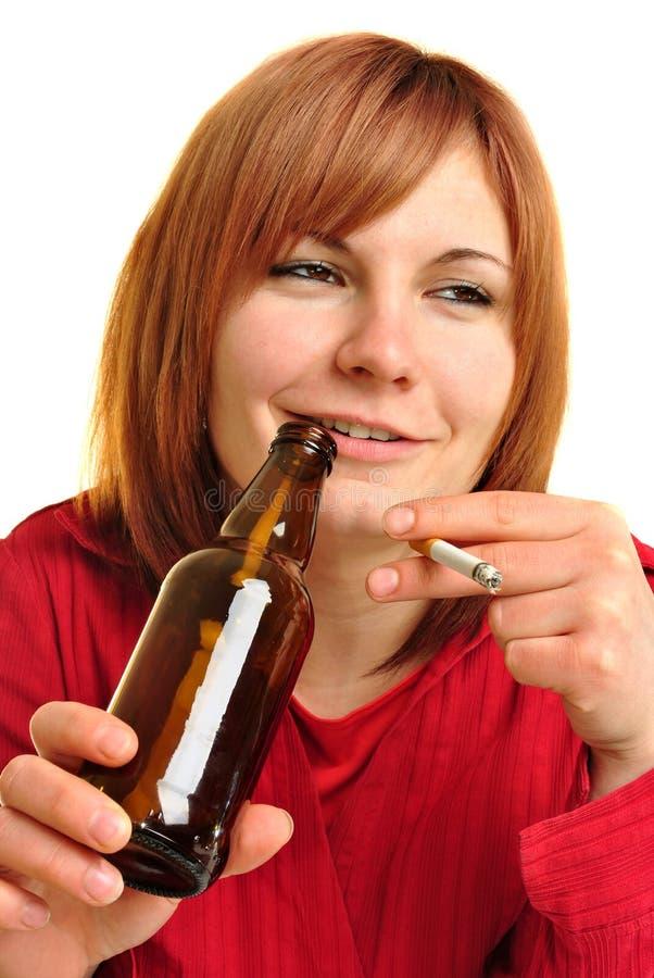 Mulher bêbedo com um frasco e um cigarro fotos de stock royalty free