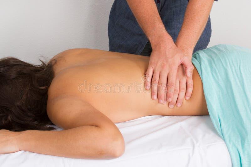 Mulher beautifulCaucasian nova que toma o procedimento da massagem de um pro massagista imagens de stock