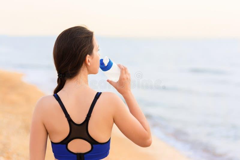 A mulher bebe a água na praia do mar foto de stock
