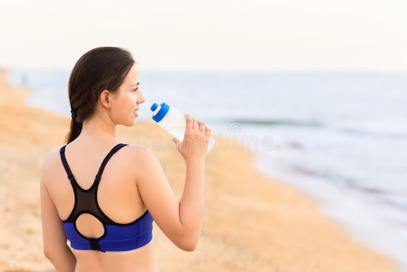 A mulher bebe a água na praia do mar imagem de stock royalty free