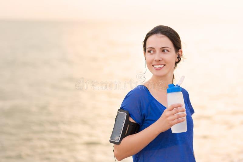 A mulher bebe a água na praia do mar fotografia de stock royalty free