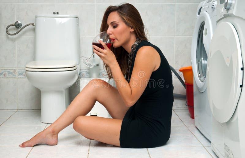 A mulher bebe o vinho em seu banheiro fotografia de stock